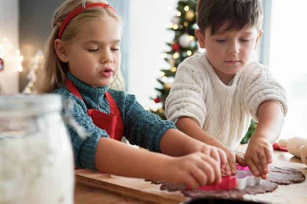 Двое детей вырезают имбирное печенье