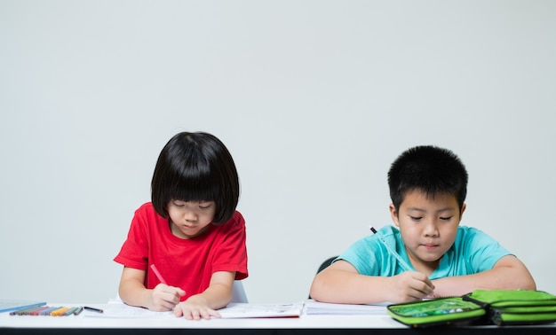 Two children doing homework together, kid write paper, family concept, learning time, student reading book, back to school