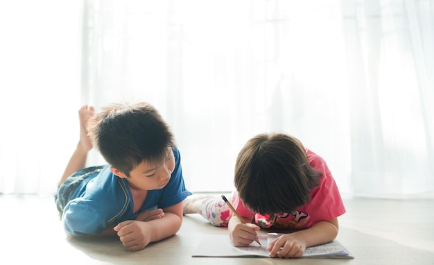 Two children doing homework together kid write paper