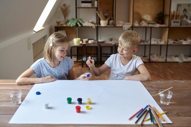 Двое детей рисуют гуашью за столом