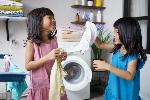 세탁실에서 옷을 씻고 웃음을 짓는 재미 행복 소녀 두 아이
