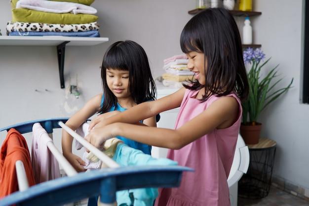Двое детей веселятся, счастливая маленькая девочка стирает одежду и смеется в прачечной