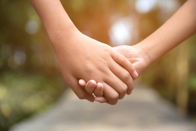 Two children holding hands each other on the wooden way