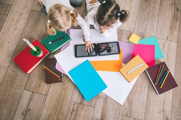 Двое детей, маленькие девочки дошкольного возраста смотрят планшет дома на полу