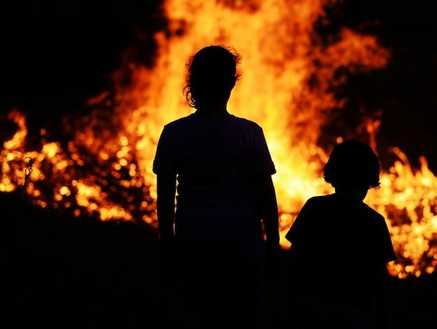Двое детей, смотрящих на большой огонь