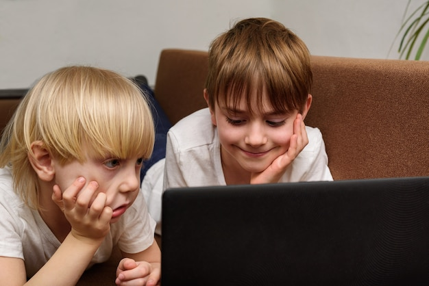 Two children lying on couch propping his head with his hands and looking at monitor.