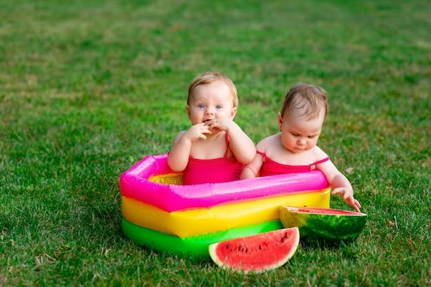 즐거운 쌍둥이의 두 자녀는 여름에 풍선 수영장에서 수박과 텍스트를 위한 공간이 있는 푸른 잔디에서 수영합니다