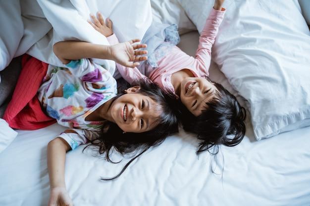 Двое детей играют и смеются в постели