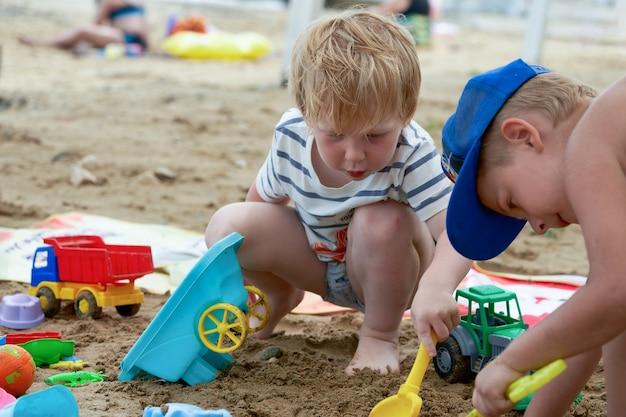 두 아이가 플라스틱 장난감을 가지고 모래에서 놀고 있다