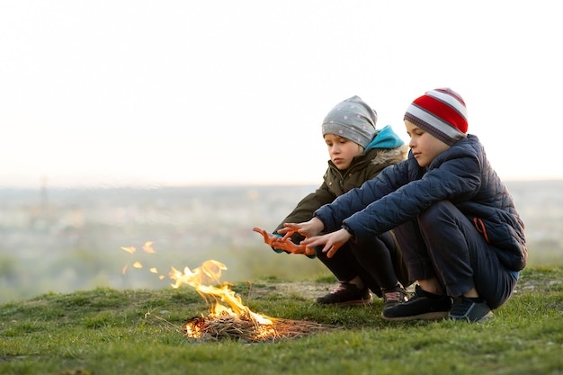 Two children playing with fire outdoors in cold weather.