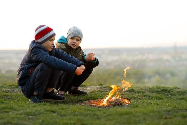 Двое детей играют с огнем на открытом воздухе в холодную погоду.