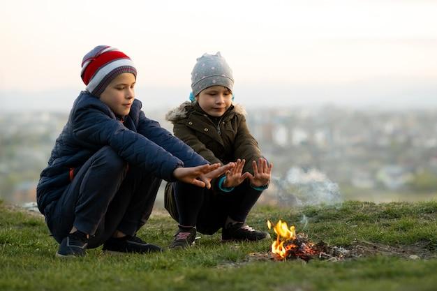 寒い季節に屋外で火遊びをしている2人の子供。