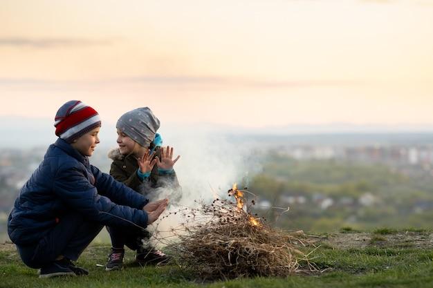寒い季節に屋外で火遊びをする2人の子供。