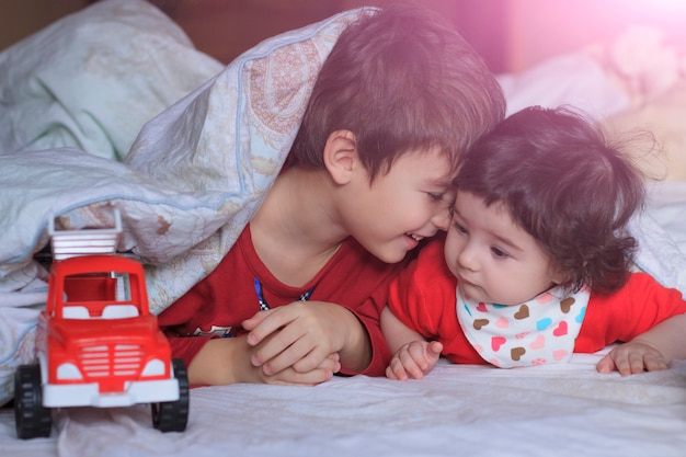 Two children in red clothes are lying under a light blanket
