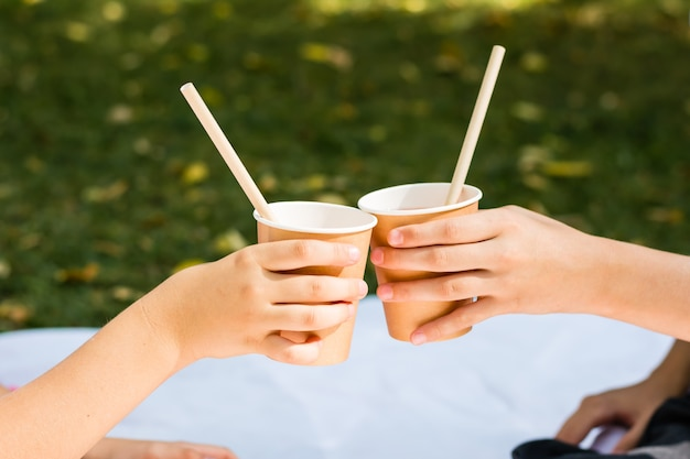 Two children's hands are holding eco-friendly cups and tubes with apple juice at a picnic in the park. eco-friendly disposable tableware