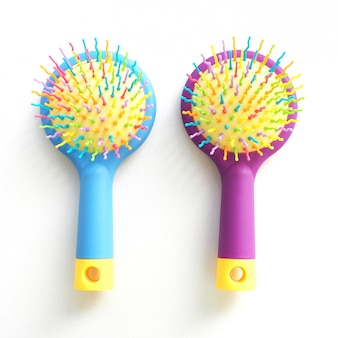 Two children's massage combs with curved multi-colored teeth. isolated