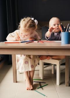 집에서 연필로 함께 그림을 그리는 두 아이의 여동생과 소년 형제