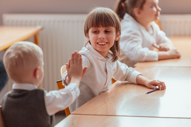 Two children sit at a school table and give high five