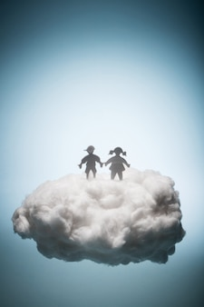 Two children standing on a white cloud.