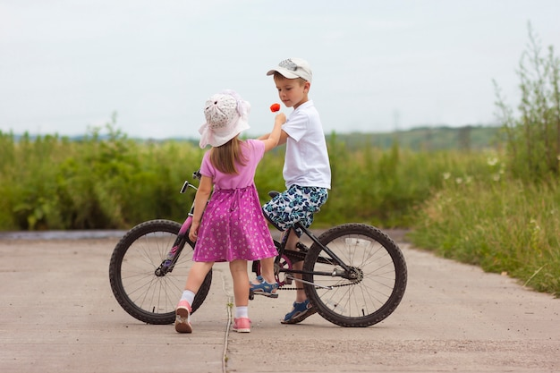 Two children in summer day bicycle and flower boy and girl
