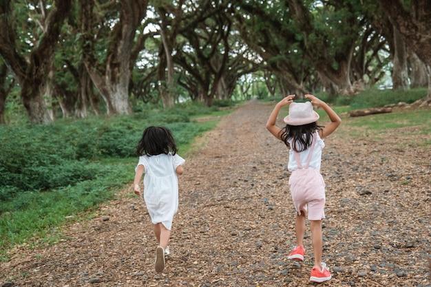 Двое детей уходят между тенистыми деревьями