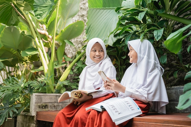 Two children wearing headscarves in school uniforms using a smartphone and a book while chatting whi...