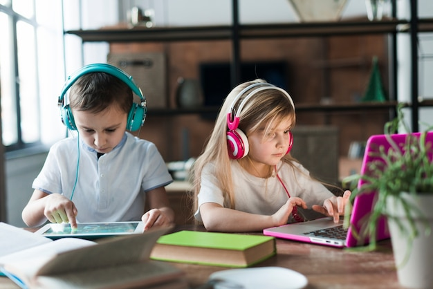 Two children with laptop and tablet