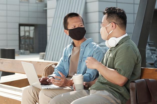 토론을 하는 보호 마스크를 쓴 두 명의 중국 사업가