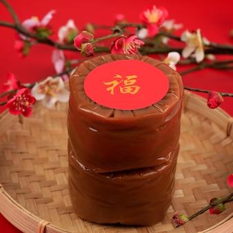 Два китайских новогодних торта (китайский иероглиф «фу» означает удачу). популярный как куэ керанжанг или додол китай в индонезии. подается на бамбуковой тарелке, украшение из цветов имлек