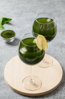 와인 글라스에 두 개의 클로렐라 음료가 레몬을 장식합니다.