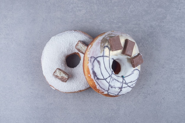 Two chocolate-adorned donuts on marble surface