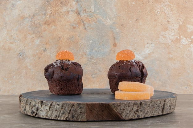 Two chocolate brownies with marmalades on wooden piece