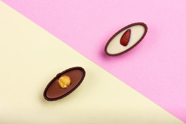 色付きの背景にナッツと2つのチョコレート菓子斜めの背景黄色のピンク