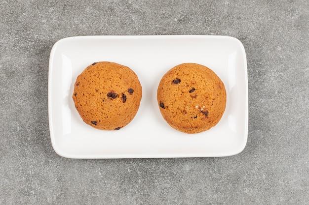 Два шоколадных печенья на белой тарелке.