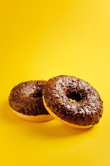Two chocolate donuts on yellow background