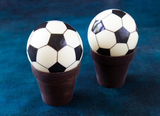 초콜릿 냄비에 두 개의 초콜릿 축구 공 케이크. 아름다운 파란색 테이블에 어린이 축구 팬을위한 달콤한 선물