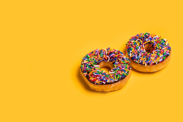 Two of chocolate frosted donuts with sprinkles on yellow background.