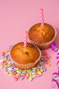Two chocolate muffins, a birthday candle. party for girls. caps and tinsel and multi-colored sweets on a pink background.