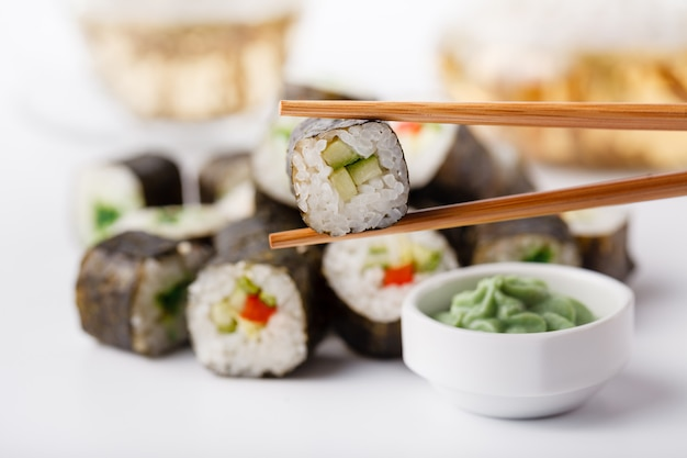 Две палочки для еды с рулетом из осомаки с овощами и разные суши с морепродуктами