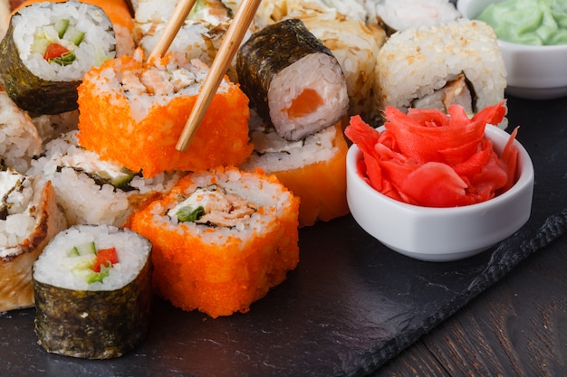 Two chopsticks holding hosomaki roll with vegetables and different sushi rolls with seafood