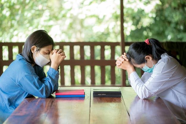 두 기독교인이 가정에서 함께 격려하고 지원하기 위해 기도하고 있습니다.