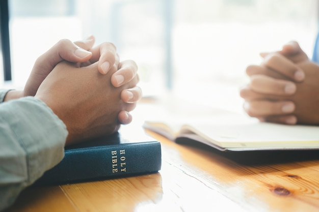 Two christian people are praying together over holy bible.