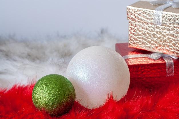 ギフトボックス付きの赤と白の毛皮の2つのクリスマスボール。白と緑のボール。金と赤のボックス。ホリデーカード。ボールに選択的に焦点を当てます。スペースをコピーします。