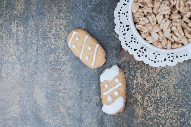 Два рождественских печенья и миска сладкого арахиса на мраморной поверхности. фото высокого качества