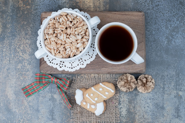 Два рождественских печенья, чашка чая и сладкий арахис на деревянной доске. фото высокого качества