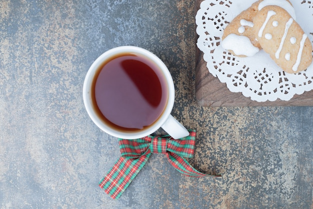 Two christmas cookies and cup of tea on marble background. high quality photo