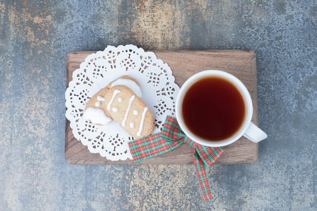Two christmas cookies and cup of tea on wooden board. high quality photo