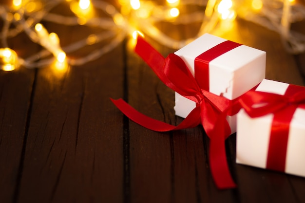 Two christmas gifts on a wooden table with bokeh lights
