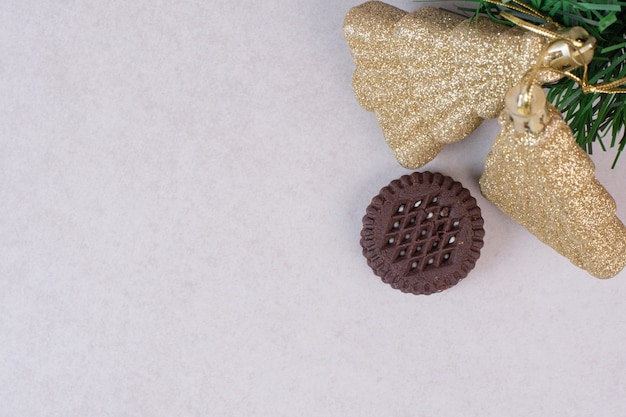 Two christmas golden decorations with cookie on white surface