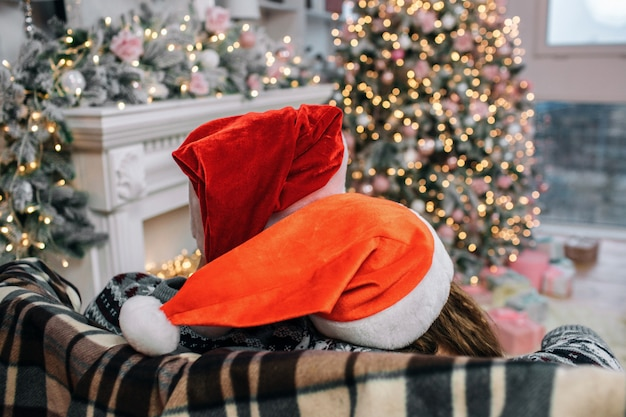 Two christmas hats are on people's head. she leans to him. they sit on sofa. people are in decorated christmas room.